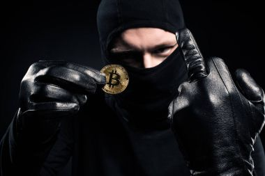 Man in black balaclava holding golden bitcoin and showing middle finger