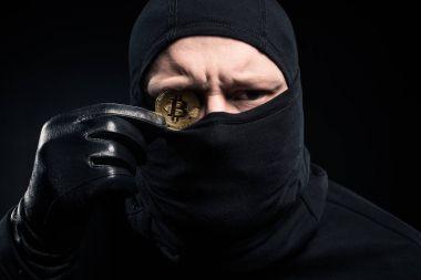 Criminal in black balaclava holding golden bitcoin