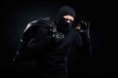 Man in balaclava holding plastic bag with cash and bitcoin