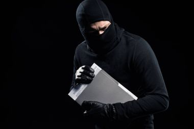 Burglar in balaclava holding top secret documents