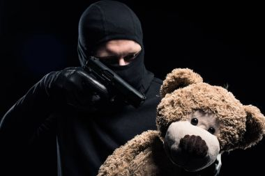 Robber in balaclava aiming at teddy bear