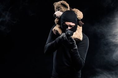 Man with teddy bear on his neck aiming with gun