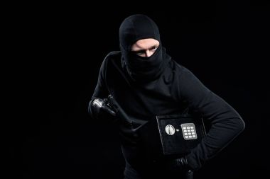 Burglar in balaclava holding gun and locked safe