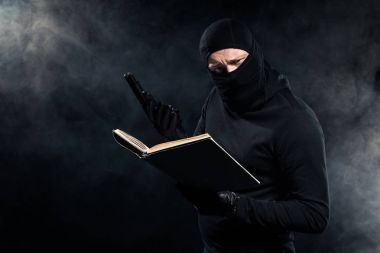 Man in black balaclava holding gun and reading book