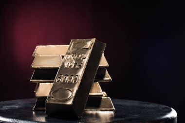 Stack of golden ingots on table against red background