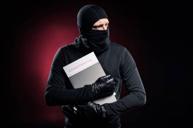 Criminal in balaclava holding confidential documents