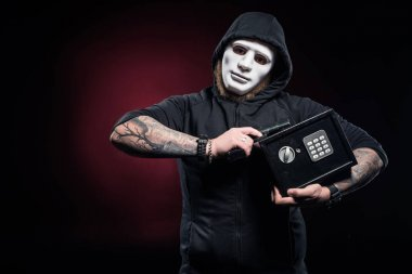 Burglar in mask holding gun and locked safe