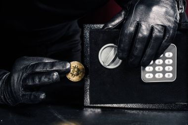 Male hand stealing golden bitcoin from safe
