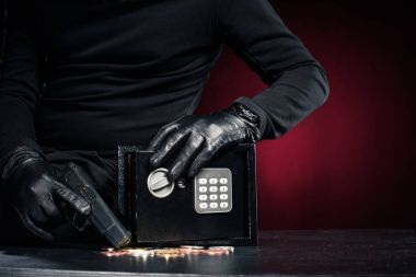 Close-up view of robber with gun taking bitcoin from safe