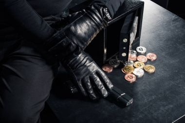 Close-up view of criminal opening safe with bitcoin cryptocurrency