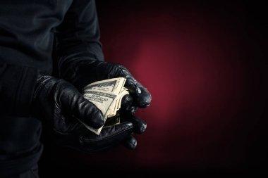 Man in black gloves holding dollar banknotes