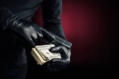 Cropped view of gun and dollars in hands of robber