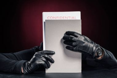 Criminal in black gloves holding confidential documents stock vector