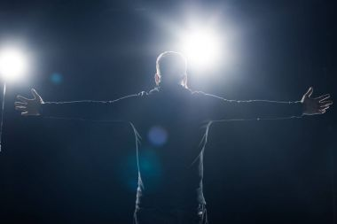 Man in black clothes standing with outstretched arms in bright light
