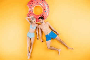 happy young couple in swimwear smiling each other while lying on swimming ring on yellow