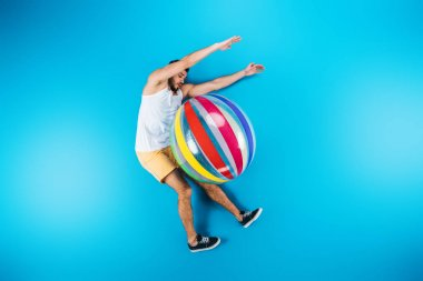 handsome young man resting with beach ball on blue, summer vacation concept