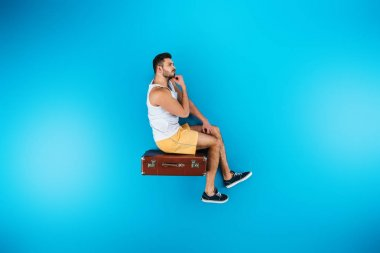 handsome young man sitting on suitcase on blue, summer vacation concept