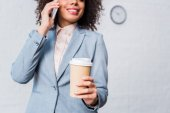 Fotografie Young businesswoman with coffee cup talking on phone