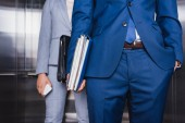Fotografie Cropped view of businessman with folders and woman with briefcase riding an elevator