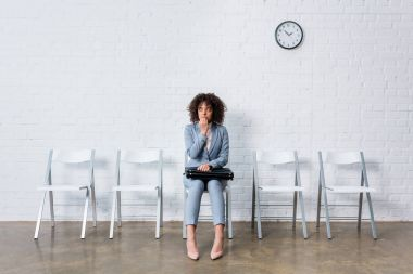 Stressed woman in suit sitting on chair with briefcase and waiting