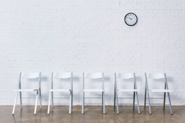 Row of empty chairs by white brick wall with clock