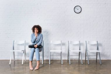 Scared businesswoman with briefcase sitting on chair and waiting