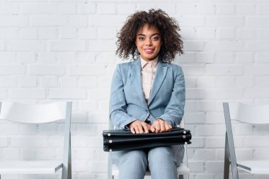 Smiling female candidate with briefcase waiting for interview while sitting on chair