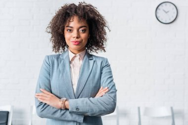 Attractive african american businesswoman standing with folded arms