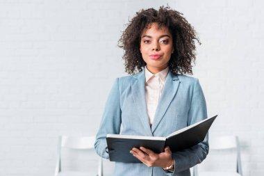 Confident African american businesswoman holding folder stock vector