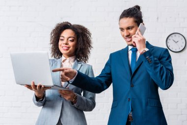 Businessman talking on phone and businesswoman looking at laptop