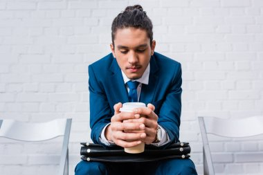 African american man in suit sitting on chair and waiting with coffee cup and briefcase in hands