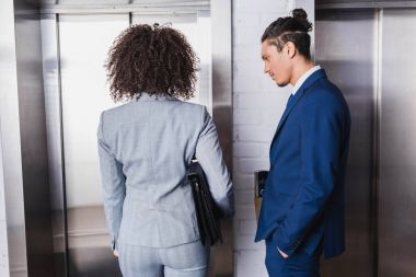 African american businesswoman with briefcase and man in suit standing by elevator