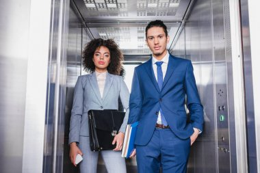 African american businesswoman with briefcase and man with folders riding an elevator stock vector