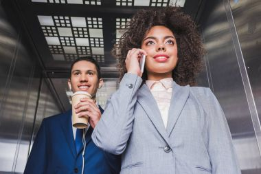 African american man in earphones with coffee cup standing in elevator with woman talking on phone