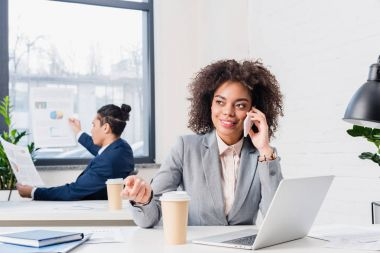 Businesswoman talking on phone with businessman working with papers behind