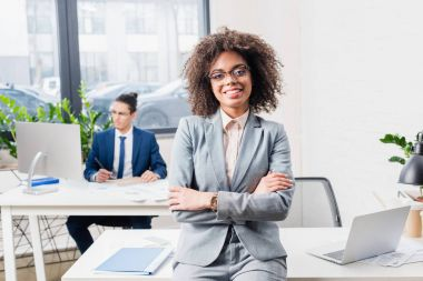 Smiling businesswoman standing in office with her male coworker by table with computer stock vector