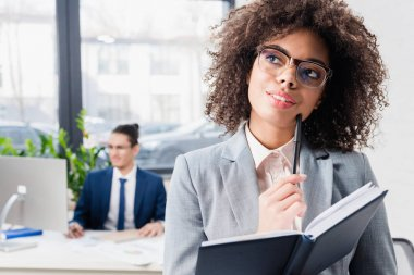 Dreamy girl holding notebook and thinking in modern office