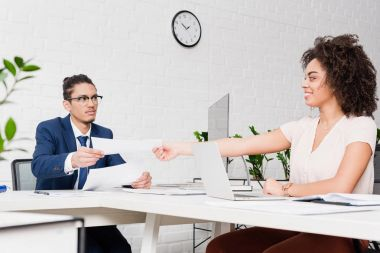 Businesswoman passing papers to businessman by working table