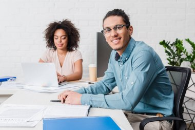 Smiling businessman working in office with female coworker by table with laptop