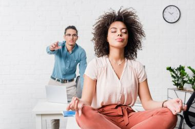 Young businesswoman relaxing and meditating in office with male coworker behind