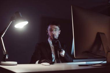 portrait of spy agent showing silence sign at table with computer screen in dark