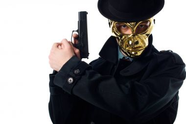 Portrait of criminal in golden mask, hat and black coat with gun in hands looking at camera isolated on white stock vector