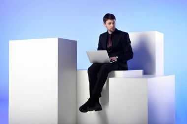 businessman with laptop sitting on white block isolated on white