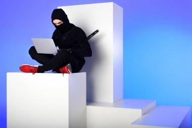 ninja in black clothing using laptop while sitting on white block isolated on blue