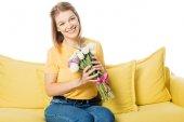 Fotografie portrét krásné usmívající se žena s kyticí tulipánů sedí na měděně izolované na bílém