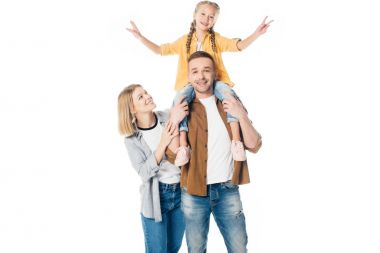 smiling father and daughter piggybacking with mother standing near by isolated on white