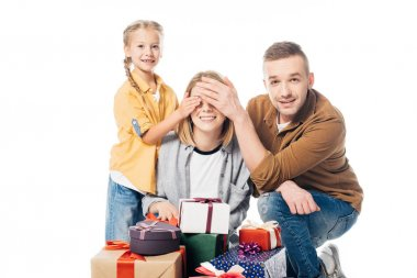 man and kid covering mothers eyes to make surprise isolated on white