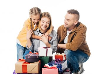 portrait of smiling family and pile of wrapped gifts isolated on white