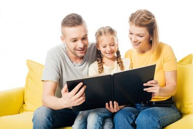 happy family looking at photos in photo album together while sitting on yellow sofa isolated on white
