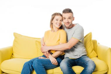 portrait of happy couple resting on yellow sofa isolated on white
